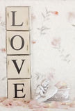 Love Cupid. The word love next to a small cupid figure and pink rose petals royalty free stock photo