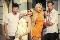 Love, date, romance concept. Sensual twins women meet men lovers on street. Friends, friendship, relations, relationship. couples on sunny summer day. Youth stock photography