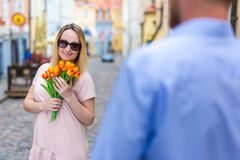 Love, dating and relationship concept - young man giving flowers. Love, dating and relationship concept - young men giving flowers to his girlfriend or wife in Stock Photography