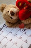Love day - Paper red hearts marking 14 february Valentines day on white calendar with soft toy Teddy bear holding red heart. Valentines`s day concept stock photos