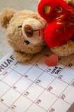 Love day - Paper red hearts marking 14 february Valentines day on white calendar with soft toy Teddy bear holding red heart. Valentines`s day concept stock photography