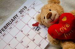 Love day - Paper red hearts marking 14 february Valentines day on white calendar with soft toy Teddy bear holding red heart. Valentines`s day concept royalty free stock photography