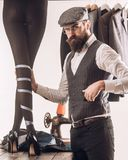 We love designer. Womens tailor making designer collection of fashion dresses. Bearded man dressmaking female clothes in stock images