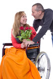 In love despite Handicap. Female in a wheelchair looking at a man Royalty Free Stock Image