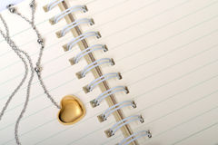 Love Diary. A golden heart necklace on a empty page of diary Stock Image