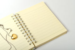 Love Diary. A golden heart necklace on a empty page of diary Stock Photography