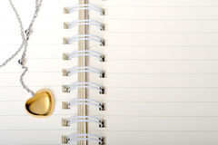 Love Diary. A golden heart necklace on a empty page of diary Stock Photos