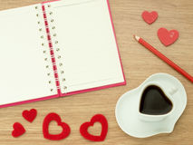 Love diary. Valentines day background with heart shape of cup with coffee, red hearts, book for diary and color pencils on wood fl Stock Images