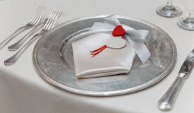 Love Dinner plate setting. Silver and white table setting with romantic red heart shape Stock Photo