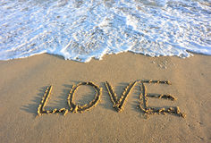 Love drawn on the beach. And sea water Royalty Free Stock Photos