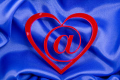 Love e-mail. Concept shot. @ at symbol inside of a red heart shape on a blue silk background royalty free stock photography