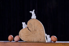 Love for Easter. Still life of a wooden heart in the sun, some Easter bunnies around it and some natural eggs Royalty Free Stock Images