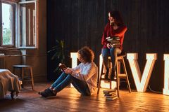 Young student couple reading together in a room decorated with voluminous letters with illumination. stock photo