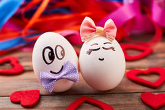 Love eggs and red hearts. Bows on eggs with faces. Art and food stock images