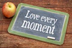 Love every moment advice on blackboard Stock Photos