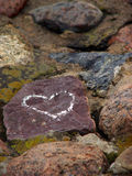 Love is everywhere. Someone left the sign of his love on one of the river bank stones Stock Photos