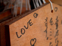 Love...everywhere. A detail of a small wishing wooden board in a Japanese temple Royalty Free Stock Photo