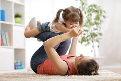 Love and family people concept - happy mom and child daughter having a fun at home stock photos