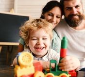 Love and family games concept. Mom, dad and boy. On light background build out of toy blocks. Parents watch their son with happy face making brick constructions royalty free stock image