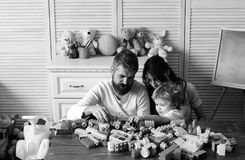 Love and family games. Parents and son with busy faces. Love and family games concept. Parents and son with busy faces make brick constructions. Mom, dad and boy stock images