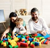 Love and family games concept. Young family spends time. In playroom. Parents and son with happy faces make brick constructions. Mom, dad and kid with toys on stock photography