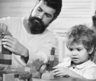 Love and family games. Parent and son with busy faces. Love and family games concept. Parent and son with busy faces make brick constructions. Young family stock photos