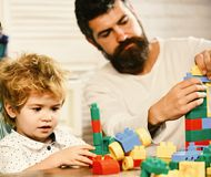 Love and family games. Parent and son with busy faces. Love and family games concept. Parent and son with busy faces make brick constructions. Young family stock photo