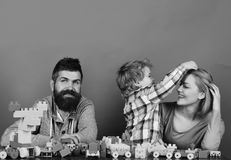 Love and family games. Young family spends time in playroom. Love and family games concept. Young family spends time in playroom. Mom, dad and boy play on red stock photo