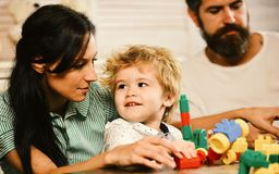 Love and family games. Young family spends time in playroom. Love and family games concept. Young family spends time in playroom. Mom, dad and boy on wooden royalty free stock image