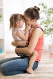 Love and family people concept - happy mother and child daughter hugging at home stock photography