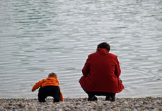 Love / Father And Son At The Lake Shore. Father plays with his son at the rocky lake shore Stock Photo
