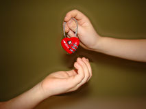 Love. The feeling of love passed from hand to hand in the shape of a heart Stock Images