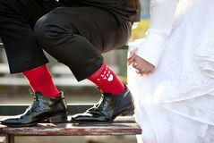 Love feet. Groom's funny feet with love sign on red socks Royalty Free Stock Images
