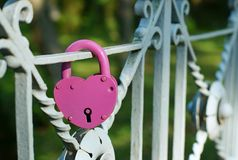 Love and fidelity symbol. The lock of red color closed on the bridge as a symbol of love, fidelity and devotion Stock Photography