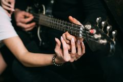 Love filled with music. Couple of musicians enjoy playing music. Couple in love play duets. Male and female hands play. The electric guitar. Couple of guitar stock photo