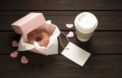 Love at first bite. Creative valentine concept photo of donut with take away coffee on wooden background Stock Photography
