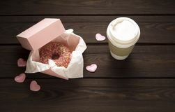 Love at first bite. Creative valentine concept photo of donut with take away coffee on wooden background Stock Image