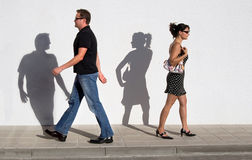 Love at first sight. A young man and a young woman walk past each other, their shadows turn Stock Image