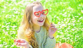 Love from first sight concept. Child posing with cardboard heart shaped eyeglasses. Girl on happy face spend leisure royalty free stock images