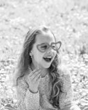 Love from first sight concept. Child posing with cardboard heart shaped eyeglasses. Girl sits on grass at grassplot royalty free stock photography