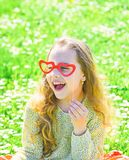 Love from first sight concept. Child posing with cardboard heart shaped eyeglasses. Girl sits on grass at grassplot stock images