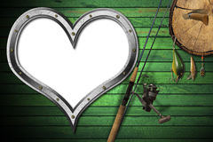 Love Fishing Tackle. Empty metal porthole heart shape on green wooden wall with fishing tackle, fishing rod and pen knife Stock Photo