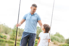 We love fishing together. Cheerful father and son holding fishing rods and looking at each other with smile while standing at the riverbank together Stock Image