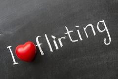 Love flirting. I love flirting phrase handwritten on school blackboard Stock Image
