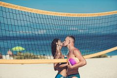 Love and flirting of couple. woman and muscular man with ball at net. Summer vacation and travel on holiday in. Love and flirting of couple. women and muscular stock photos