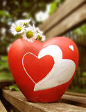 Love and Flowers. Heart shaped ceramic vase containing flowers on a bench Royalty Free Stock Photography