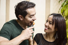 Love and food. Couple eating fruit in the kitchen Royalty Free Stock Photos