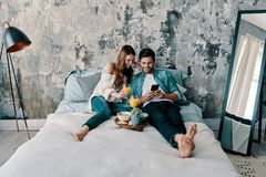 Love forever. Beautiful young couple having breakfast while spending time in bed at home royalty free stock photo