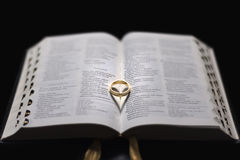 Love forever. Wedding ring on Holy Bible forming a heart. Shallow depth of field Stock Images