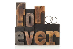 Love forever. Wedding rings on the word forever, written with vintage letterpress printing blocks royalty free stock photos